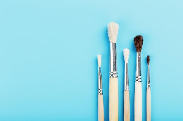 Borstels voor tekenen met verf gemaakt van natuurlijk hout en wol op een blauwe achtergrond.