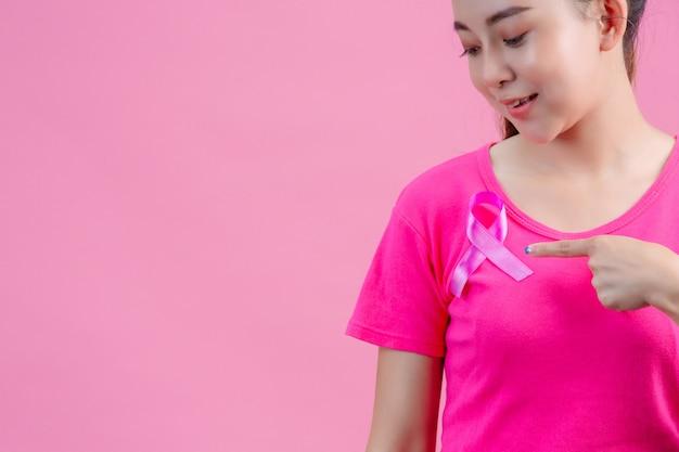 Borstkanker bewustzijn, vrouw in roze t-shirt met satijn roze lint op haar borst, ter ondersteuning van symbool borstkanker bewustzijn