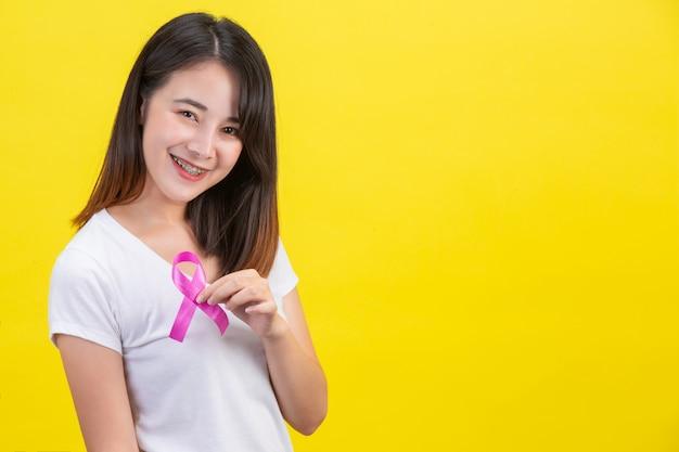 Borstkanker, een vrouw in een wit t-shirt met een satijnen roze lint op haar borst, een symbool voor bewustzijn van borstkanker