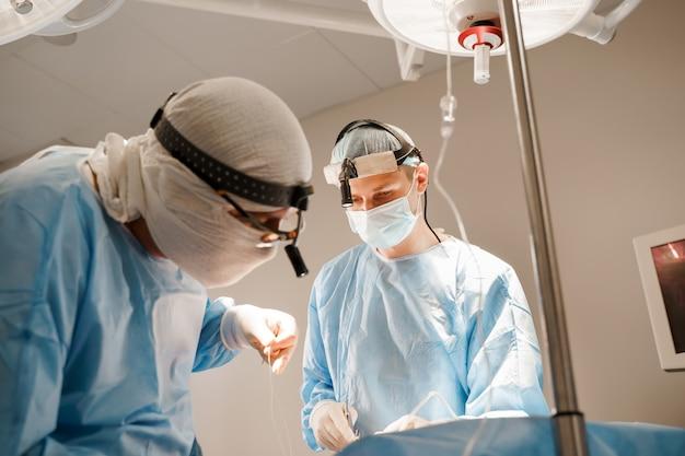 Borstvergroting plastische operatie en correctie in medische kliniek. chirurg plaatst siliconenimplantaat in de borst van de vrouw.
