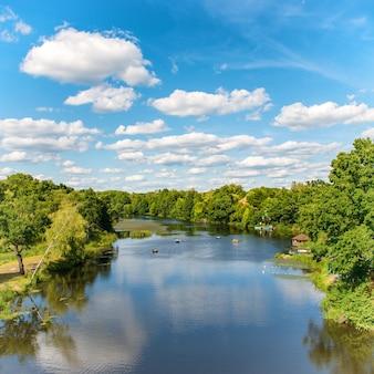 Bos aan de rivier met blauwe lucht en landschap van wolken