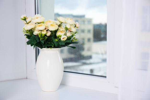 Bos gele rozen in keramische vaas op een raam
