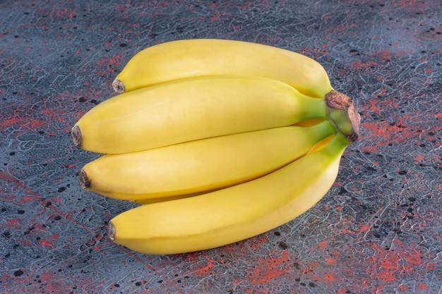 Bos van bananen die op kleurrijk oppervlak worden geïsoleerd