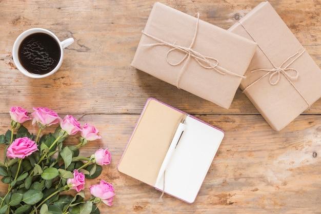 Bos van bloemen met geschenkdozen; dagboek en zwarte thee op houten achtergrond