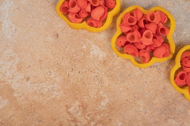 Bos van deegwaren in paprikaplakken op oranje achtergrond