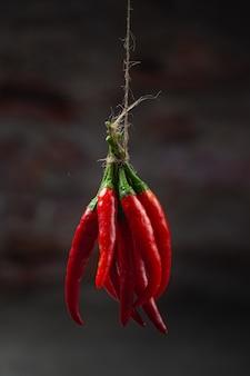 Bos van gedroogde roodgloeiende chili peper op zwart.