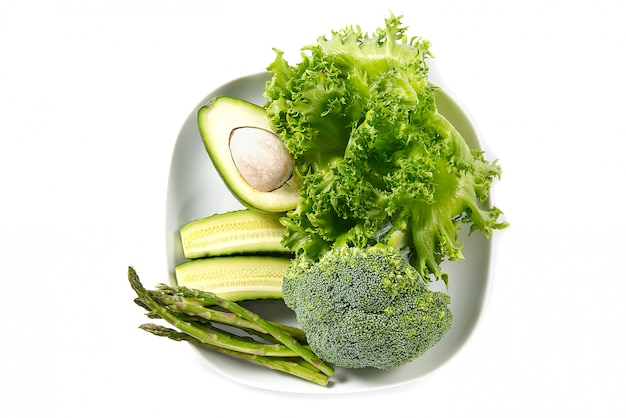 Bos van geïsoleerde groenten. stapel van verse groenten op witte plaat. groene groente dieet.