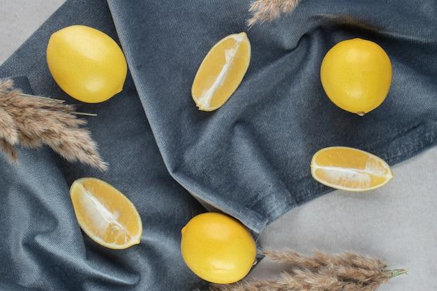 Bos van gele citroenen op blauwe doek.
