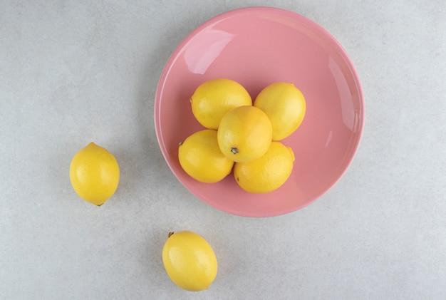 Bos van gele citroenen op roze plaat.