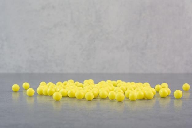 Bos van gele pillen op marmeren tafel.