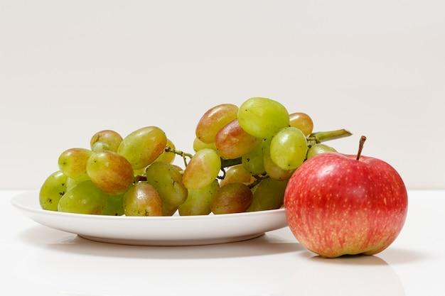 Bos van groene druiven en appel op witte plaat.