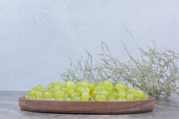 Bos van groene druiven in houten kom met plant.