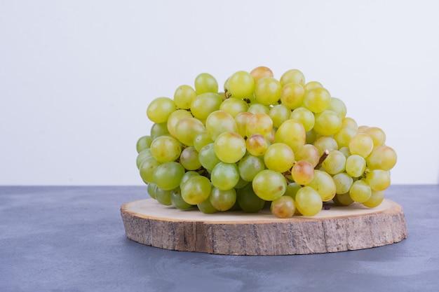 Bos van groene druiven op een houten bord.
