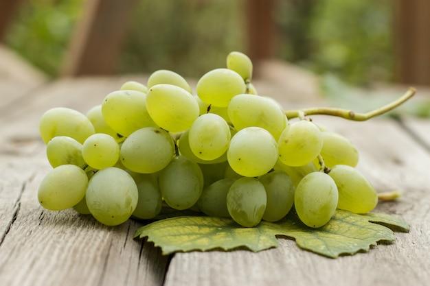 Bos van groene druiven op houten tafel