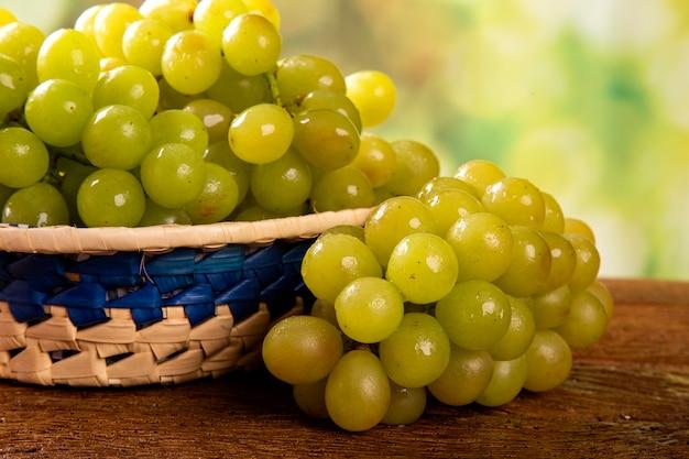 Bos van groene druiven, vruchten van de herfst, een symbool van overvloed op rustieke houten achtergrond.
