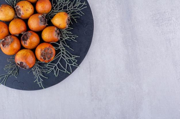 Bos van kaki's versierd met dennenbladeren op een bord op witte achtergrond.