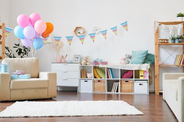 Bos van kleurrijke ballonnen en stapel geschenkdozen op fauteuil in de woonkamer versierd met vlaggen voor thuis verjaardagsfeestje