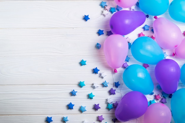 Bos van kleurrijke partijballons met document sterren op witte houten achtergrond. plat lag stijl met copyspace