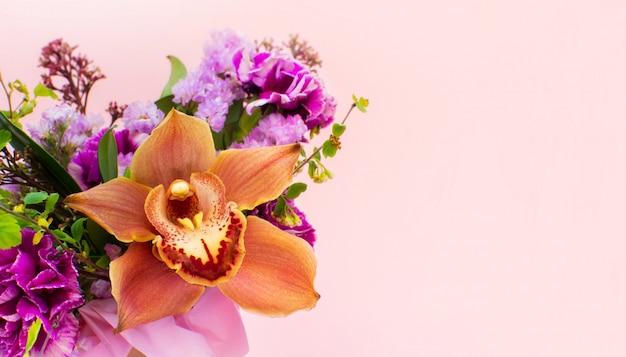Bos van mooie bloemen, orchidee die op lichtrose achtergrond wordt geïsoleerd