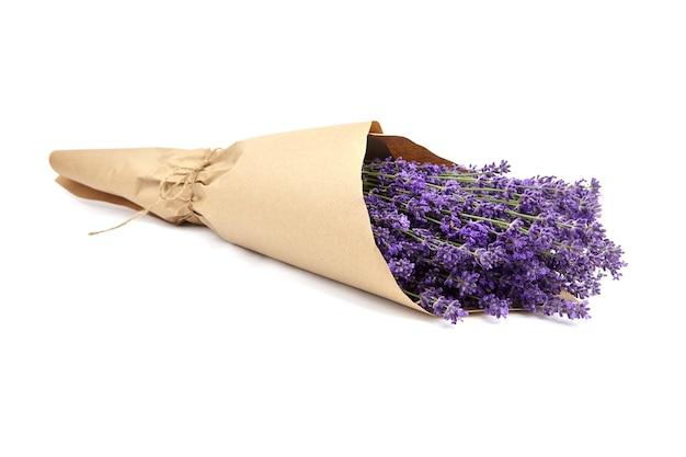 Bos van natuurlijke lavendelbloemen verpakt in ambachtelijk papier dat op wit wordt geïsoleerd
