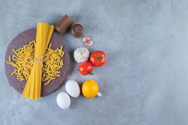 Bos van ongekookte spaghetti in touw met verse rode tomaten en knoflook.