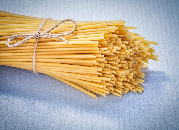 Bos van ongekookte spaghetti op blauwe achtergrond eten en drinken concept.