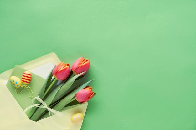 Bos van oranje tulpen in papieren zak, decoratieve paaseieren en cadeaubon, kopie-ruimte