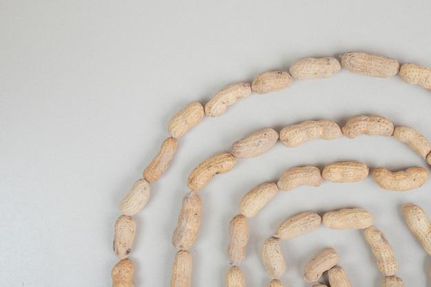 Bos van organische pinda's op beige oppervlak