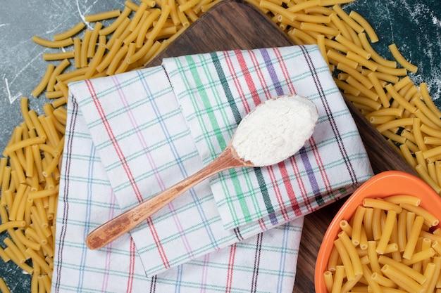 Bos van rauwe pasta op een houten bord met tafellaken en bloem. hoge kwaliteit foto