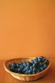 Bos van rijpe blauwe tafeldruiven in een mand met oranje muur