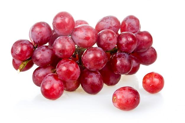 Bos van rijpe roze druiven die op witte achtergrond worden geïsoleerd