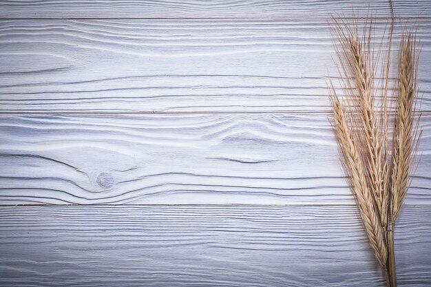 Bos van rijpe tarwe en rogge oren op een houten bord