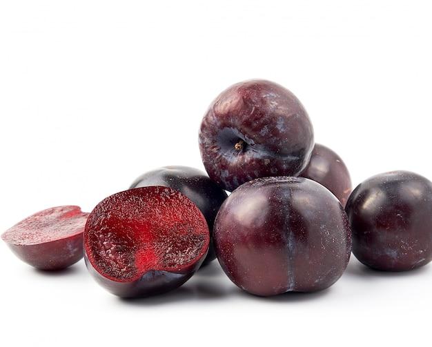 Bos van rijpe verse blauwe ronde pruimen, één vrucht wordt gesneden