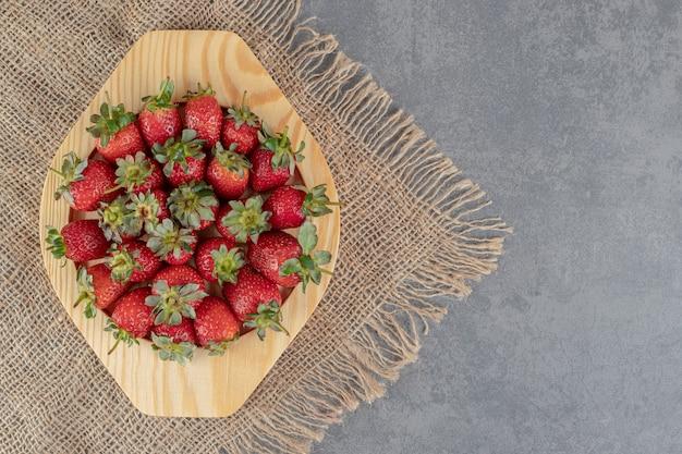 Bos van rode aardbeien op houten plaat. hoge kwaliteit foto