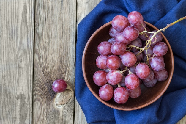 Bos van rode druiven op blauwe textiel in een kom, op een houten tafel. kopieer ruimte. rustieke stijl