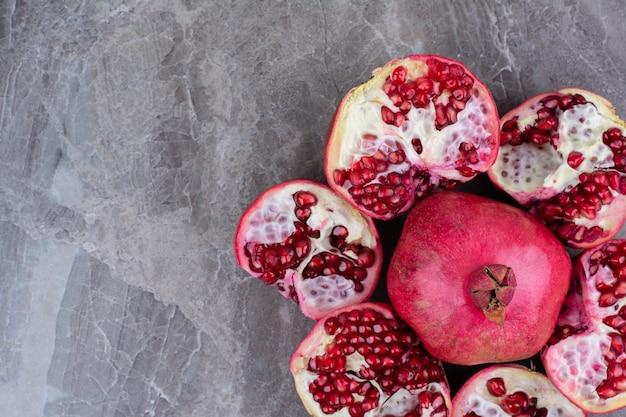 Bos van rode granaatappels op stenen achtergrond.