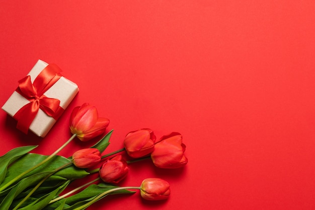 Bos van rode tulpen en geschenkdozen met rode linten op een rode achtergrond.