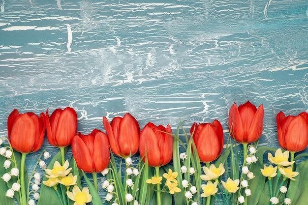 Bos van rode tulpen, gele narcissen en lelietje-van-dalenbloemen op plattelander