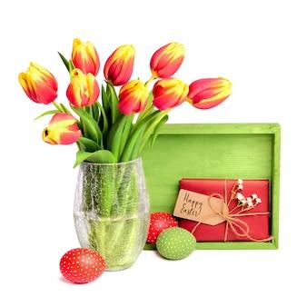 Bos van rode tulpen, houten plank, cadeau met tag en gekleurde paaseieren op wit
