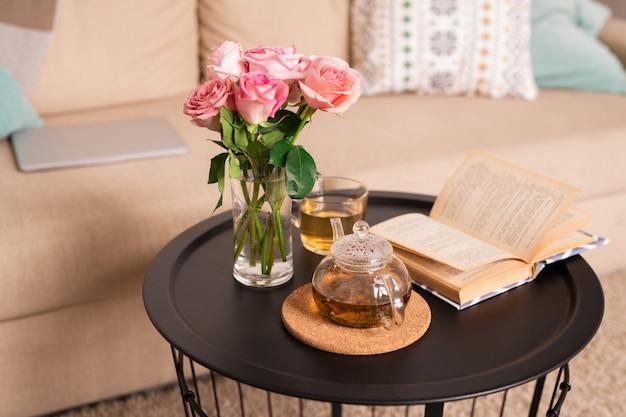 Bos van roze rozen in glas water, open boek, theepot en kopje met groene thee op kleine tafel bij comfortabele bank met kussens