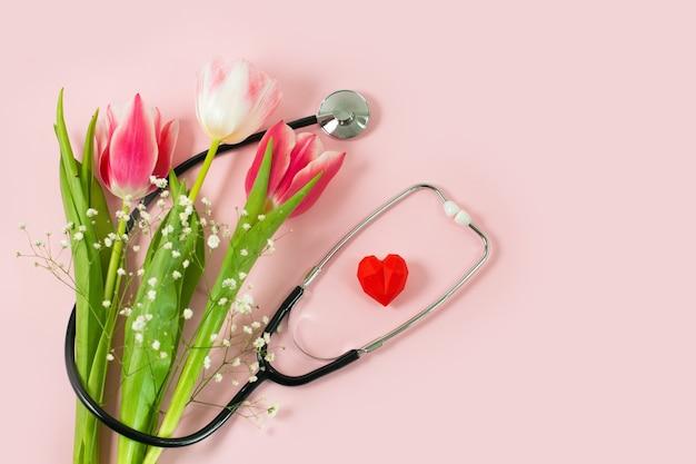 Bos van roze tulpen en stethoscoop op roze bureau.