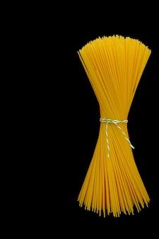 Bos van ruwe spaghetti op zwarte achtergrond