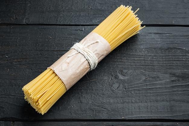 Bos van spaghetti, rauwe italiaanse pasta set, op zwarte houten tafel