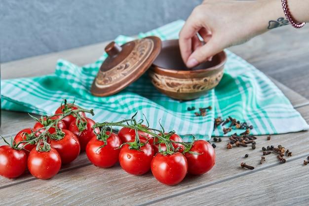 Bos van tomaten met tak en vrouwenhand die kruidnagel uit een kom op houten lijst nemen