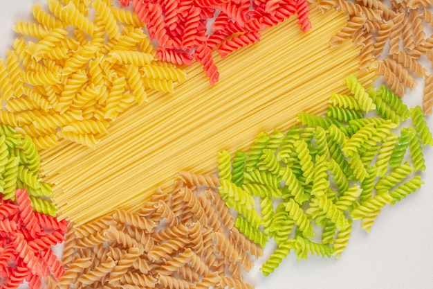 Bos van verschillende kleurrijke rauwe pasta op stenen oppervlak. Gratis Foto