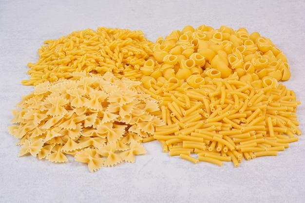 Bos van verschillende rauwe pasta op stenen oppervlak
