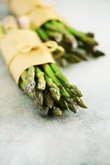 Bos van verse asperge op grijze backgrouns. asperges op ambachtelijk papier met pakket. ruw, veganistisch, vegetarisch en schoon eetconcept.