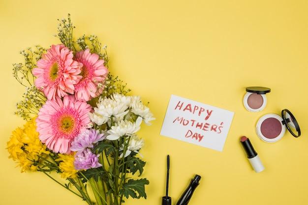 Bos van verse bloemen dichtbij document met de gelukkige woorden van de moedersdag en lippenstiften met poeder