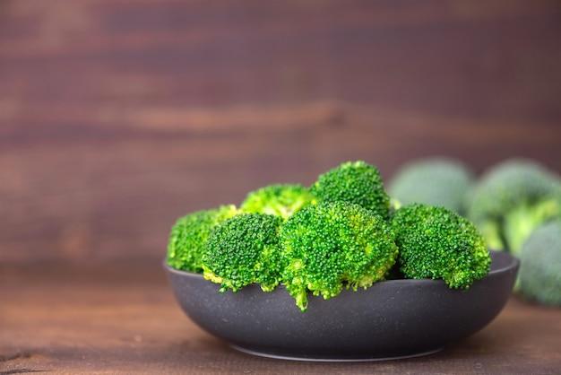 Bos van verse groene broccoli op zwarte plaat over bruin hout. zijaanzicht.