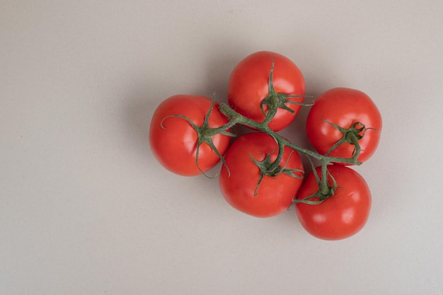 Bos van verse, rode tomaten met groene stengels op witte lijst.
